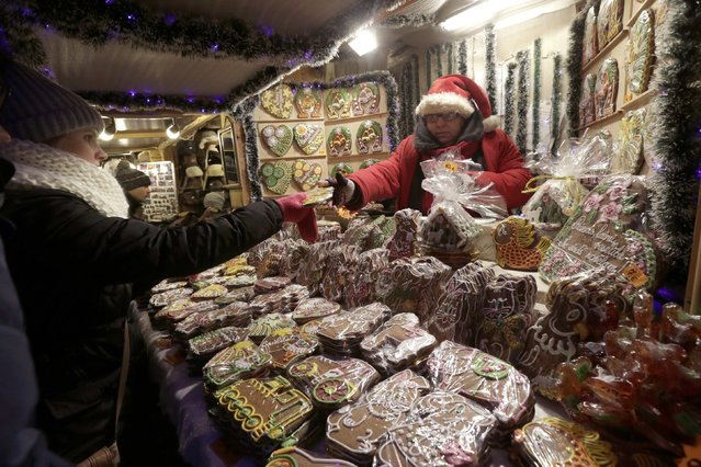 A woman buys gingerbread from a vendor wearing Santa outfit at the Christmas market in Riga, Latvia, December 6, 2014. (Photo by Ints Kalnins/Reuters)