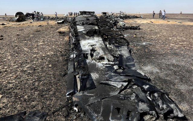 Military investigators from Egypt and Russia stand near the debris of a Russian airliner at the site of its crash at the Hassana area in Arish city, north Egypt, November 1, 2015. (Photo by Mohamed Abd El Ghany/Reuters)