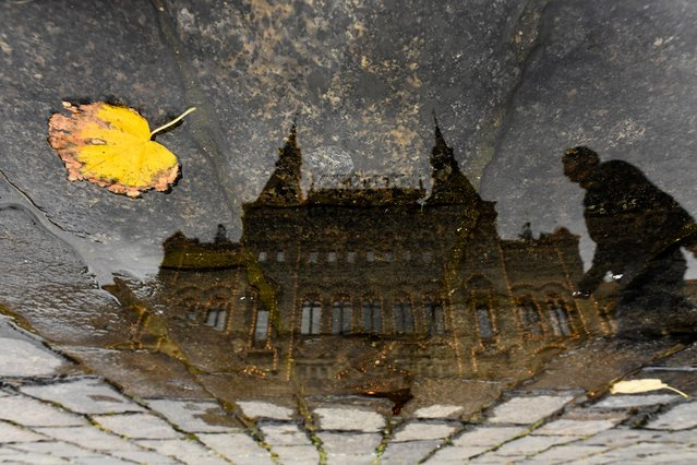 A man is reflected in a puddle as he walks past the GUM department store in downtown Moscow, Russia on October 12, 2017. (Photo by Kirill Kudryavtsev/AFP Photo)