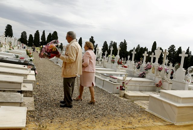 A couple visit a tomb during All Saints Day at the cemetery of San Fernando in the Andalusian capital of Seville, November 1, 2015. (Photo by Marcelo del Pozo/Reuters)
