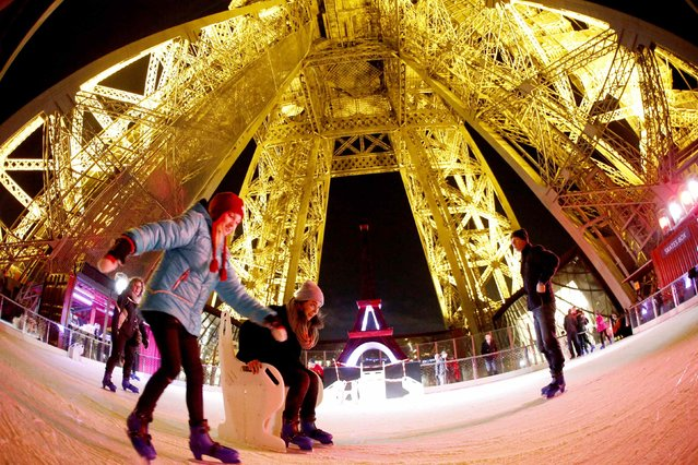 Tourists ice skate at night on the Eiffel Tower's skating rink in Paris December 9, 2014. The skating rink, located on the first level of the Eiffel Tower, opens to the public as part of the Christmas holiday season. (Photo by Charles Platiau/Reuters)