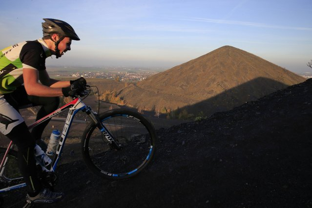 A cyclist climbs one of the twin slag heaps at the site of the 11/19 former coal mine in Loos-en-Gohelle, northern France October 31, 2015. (Photo by Pascal Rossignol/Reuters)