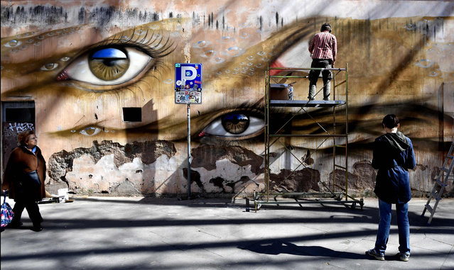 People walk past a mural by artist My Dog Sighs in Rome on March 14, 2018. (Photo by Tiziana Fabi/AFP Photo)