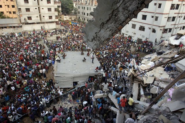 Rescue workers try to rescue trapped garment workers in the Rana Plaza building which collapsed, in Savar, 30 km (19 miles) outside Dhaka April 24, 2013. A block housing garment factories and shops collapsed in Bangladesh on Wednesday, killing nearly 100 people and injuring more than a thousand, officials said. (Photo by Andrew Biraj/Reuters)