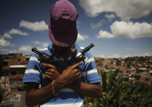 A Brazilian drug gang member nicknamed Poison, 18, poses with a gun atop a hill overlooking a slum in Salvador, Bahia State, April 11, 2013. One of Brazil's main tourist destinations and a 2014 World Cup host city, Salvador suffers from an unprecedented wave of violence with an increase of over 250% in the murder rate, according to the Brazilian Center for Latin American Studies (CEBELA). (Photo by Lunae Parracho/Reuters)