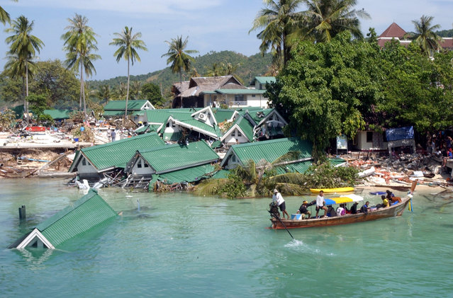 In this December 28, 2004 file photo, a boat passes by a damaged hotel, at Ton Sai Bay on Phi Phi Island, in Thailand. (Photo by Suzanne Plunkett/AP Photo)