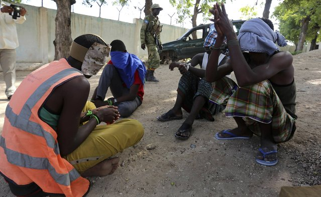 Blind-folded suspects crouch as they are detained after attackers from the militant group al Shabaab invaded the African Union's Halane base on the edge of the Mogadishu international airport compound in Somalia's capital Mogadishu, December 26, 2014. (Photo by Feisal Omar/Reuters)
