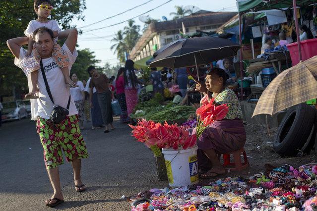 A man carries a child as a flower vendor watches in Yangon, Myanmar, Saturday, November 7, 2015. (Photo by Gemunu Amarasinghe/AP Photo)