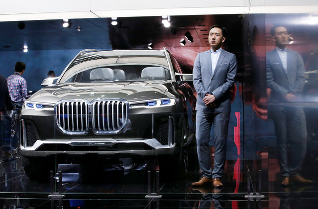 A model stands next to a BMW X7 concept car during a media preview at the Auto China 2018 motor show in Beijing, China on April 25, 2018. (Photo by Jason Lee/Reuters)