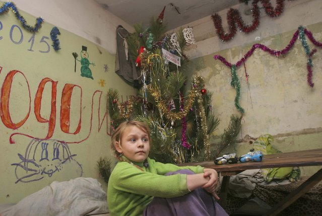 A girl sits in a basement with festive decorations used as a bombshelter in Donetsk December 30, 2014. (Photo by Igor Tkachenko/Reuters)