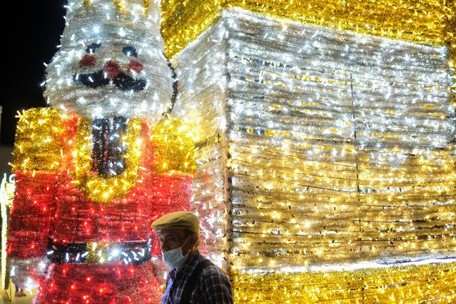 A man poses for a picture in front of Christmas lights decoration at the Francisco Morazan square in San Salvador, El Salvador, December 22, 2020. (Photo by Jose Cabezas/Reuters)