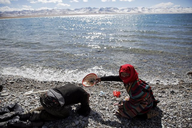 A Tibetan woman helps a man to wash his hair with water from Namtso lake in the Tibet Autonomous Region, China November 18, 2015. (Photo by Damir Sagolj/Reuters)