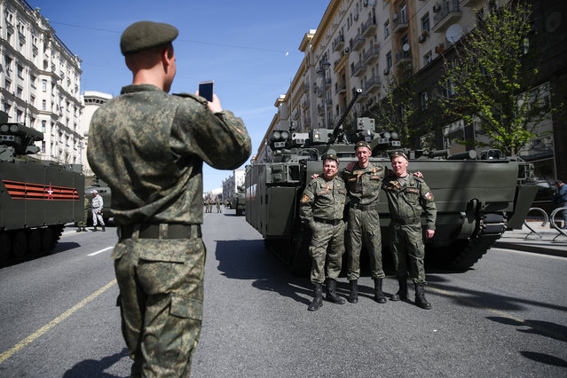 Servicemen pose for a photo by a BMP amphibious infantry fighting vehicle in Tverskaya Street ahead of a Victory Day military parade marking the 73 rd anniversary of the victory over Nazi Germany in the 1941-1945 Great Patriotic War, the Eastern Front of World War II in Moscow, Russia on May 9, 2018. (Photo by Valery Sharifulin/TASS)