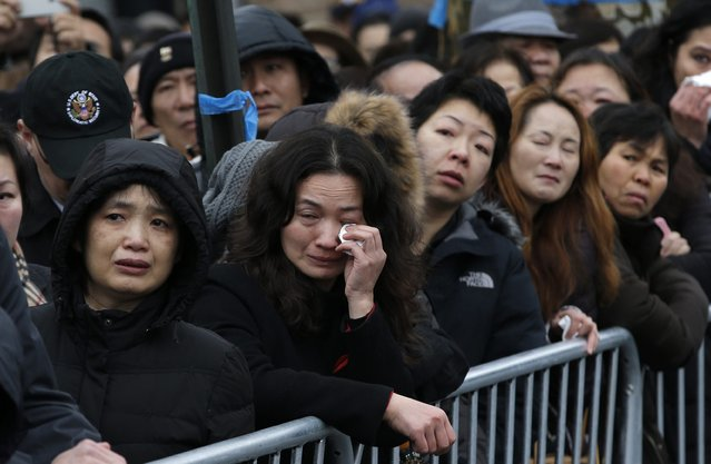 A woman wipes away tears as she and other mourners cram on the sidewalk to listen to the funeral service for New York Police Department officer Wenjian Liu in the Brooklyn borough of New York January 4, 2015. (Photo by Mike Segar/Reuters)