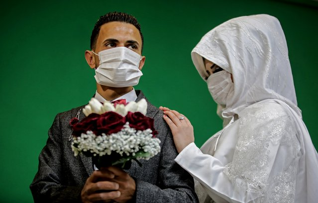 Palestinian groom Mohamed abu Daga and his bride Israa wear face masks amid the COVID-19 epidemic, during a photoshoot at a studio before their wedding ceremony in Khan Yunis in the southern Gaza Strip, on March 23, 2020. Authorities in Gaza confirmed on March 22 the first two cases of novel coronavirus, identifying them as Palestinians who had travelled to Pakistan and were being held in quarantine since their return, as the United Nations warned of potential disastrous outcomes to an outbreak given the high poverty rates and weak health system in the coastal strip, under Israeli blockade since 2007. (Photo by Said Khatib/AFP Photo)