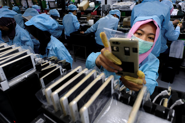 A worker holds an OPPO F1S smartphone at an OPPO smartphone factory in Tangerang, Indonesia, September 20, 2016. (Photo by Reuters/Beawiharta)