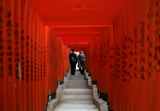 Visitors wearing protective face masks walk through red-coloured wooden torii gates at a shrine, amid the coronavirus disease (COVID-19) outbreak, in Tokyo, Japan on December 22, 2020. (Photo by Issei Kato/Reuters)
