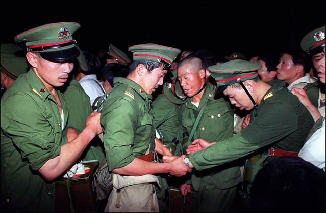 Exhausted, humiliated soldiers are hustled away by protesters in central Beijing, on June 3, 1989. (Photo by Catherine Henriette/AFP Photo)