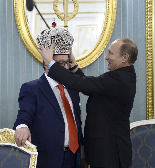 Russian President Vladimir Putin (R) puts the replica of the Russian imperial crown on Artistic Director of the Moscow State Variety Theatre and a famous entertainer and actor Gennady Khazanov, earlier received from Khazanov as a present, at the Kremlin in Moscow, Russia, December 1, 2015. The meeting was dedicated to Khazanov's 70th birthday. (Photo by Alexei Nikolsky/Reuters/Sputnik/Kremlin)