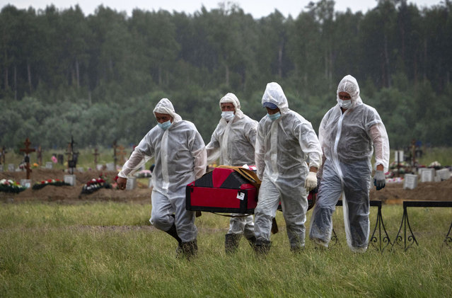 Cemetery workers wearing protective suits carry the coffin of a COVID-19 victim in the special purpose for coronavirus victims section of a cemetery in Kolpino, outside St.Petersburg, Russia, Tuesday, June 30, 2020. (Photo by Dmitri Lovetsky/AP Photo)