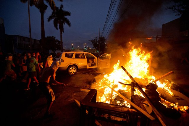 Protesters push a car towards a police line to set it on fire during a demonstration in Belo Horizonte, Brazil, Wednesday, June 26, 2013. The wave of protests that hit Brazil in mid-June began as opposition to transportation fare hikes, then expanded to a laundry list of causes including anger at high taxes, poor services and high World Cup spending, before coalescing around the issue of rampant government corruption. (Photo by Victor R. Caivano/AP Photo)