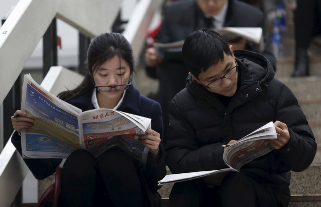 Jobseekers read papers containing jobs information during a job fair for college graduates at a exhibition centre in Beijing, China, December 5, 2015. (Photo by Reuters/Stringer)