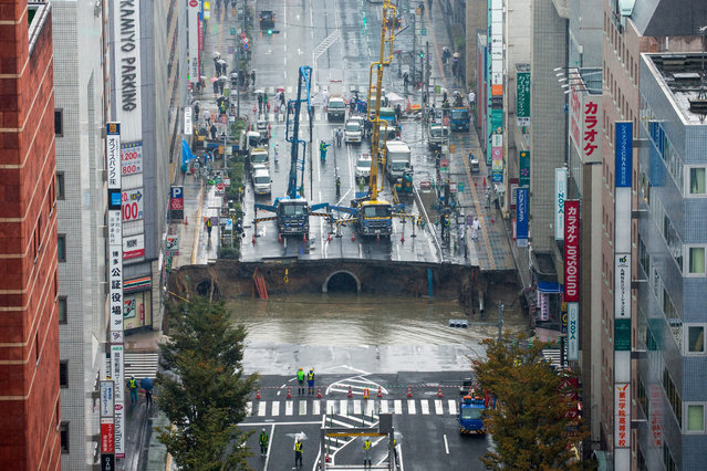 A large sinkhole cuts off an avenue in central Fukuoka, southwestern Japan, 08 November 2016. According to local media reports, the sinkhole has caused blackouts and disrupted traffic. Authorities have evacuated surrounding buildings in case of further damage. There were no immediate reports of damage or injuries. (Photo by Hiroshi Yamamura/EPA)
