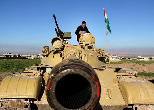 In this Tuesday, January 20, 2015 image released by the Kurdistan Region Security Council (KRSC), A Kurdish peshmerga stands on a military tank preparing for battle against the Islamic State group in northern Iraq. Kurdish Regional Security Council said Wednesday, Jan. 21, 2015 that Kurdish peshmerga fighters launched a new offensive to secure areas southeast and southwest of the dam. (Photo by AP Photo/Kurdistan Region Security Council)