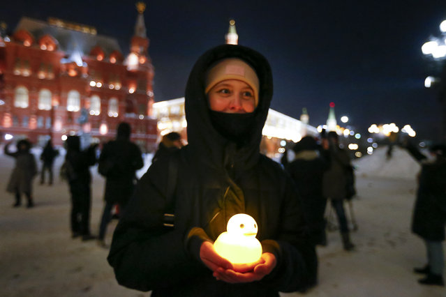 A young woman holds an illuminated duck, in support of jailed opposition leader Alexei Navalny and his wife Yulia Navalnaya near Red Square, with the Historical Museum and the Kremlin Wall in the background, in Moscow, Russia, Sunday, February 14, 2021. (Photo by Alexander Zemlianichenko/AP Photo)