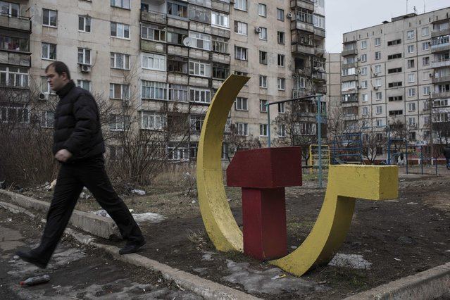 A man walks past a Soviet hummer and sickle sculpture, outside an apartment building damaged by a Grad missile in Vostochniy district of Mariupol, Eastern Ukraine, Sunday, January 25, 2015. (Photo by Evgeniy Maloletka/AP Photo)