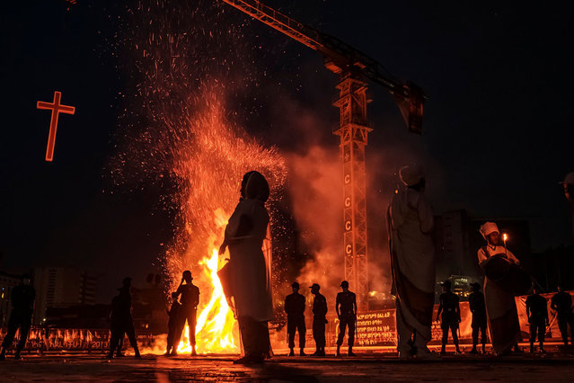 People stand in front of a bonfire during the celebration of the eve of the Ethiopian Orthodox holiday of Meskel, that commemorates the discovery in the fourth century of the True Cross by the Roman Empress Helena, in Addis Ababa, on September 26, 2020. Like most countries around the world, this annual religious event is being attended by the clergy and members of the choir only, with no public audience due to the novel coronavirus, Covid-19 pandemic. (Photo by Eduardo Soteras/AFP Photo)