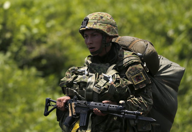 A Japanese Ground Self-Defense Force's 1st Airborne Brigade soldier walks toward a staging post after parachuting during their military drill at Higashifuji training field in Susono, west of Tokyo, July 8, 2013. Japan faces increasingly serious threats to its security from an assertive China and an unpredictable North Korea, a defence ministry report said on Tuesday, as ruling politicians call for the military to beef up its ability to respond to such threats. (Photo by Issei Kato/Reuters)