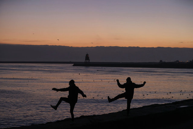 People practise Tai Chi at dawn with the Herd Groyne Lighthouse and the River Tyne in the background, in North Shields, Britain, January 15, 2021. (Photo by Lee Smith/Reuters)