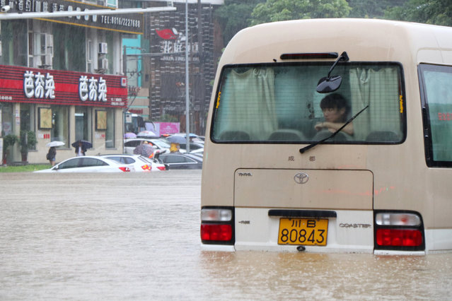 A woman watches the rain from inside a stranded vehicle on a flooded street in Mianyang, Sichuan, China on July 11, 2018. (Photo by CNS via Reuters)
