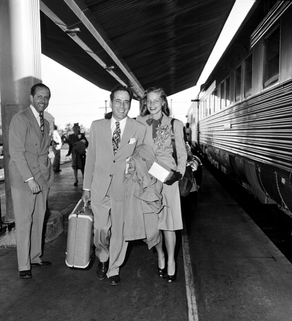 Actor Humphrey Bogart and actress Lauren Bacall are shown at a train station before they board the Santa Fe in Los Angeles, Ca., on May 18, 1945.  The couple will travel to Mansfield, Ohio, where they will get married at a friend's farm.  The person at left is unidentified. (Photo by AP Photo)