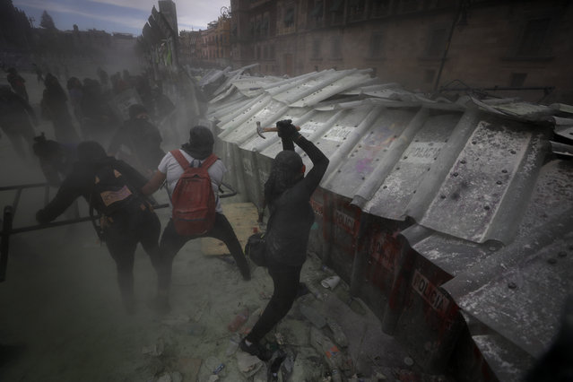 Demonstrators attack a barricade protecting Mexico City's National Palace during a march to commemorate International Women's Day and protesting against gender violence, Monday, March 8, 2021. (Photo by Rebecca Blackwell/AP Photo)