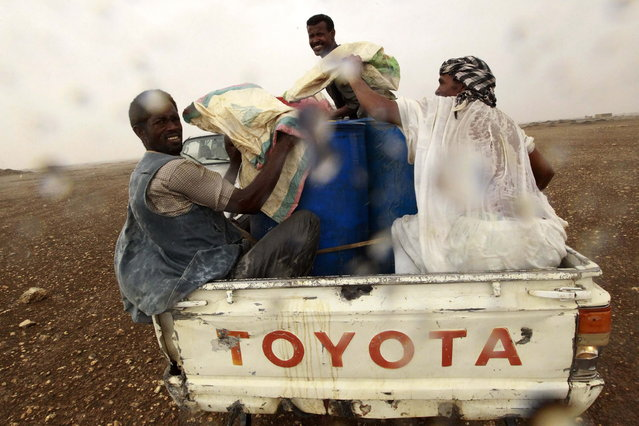 Gold mine workers at the back of a truck take cover from rain as they make their way to a local mine in Al-Ibedia locality at River Nile State, July 30, 2013. (Photo by Mohamed Nureldin Abdallah/Reuters)