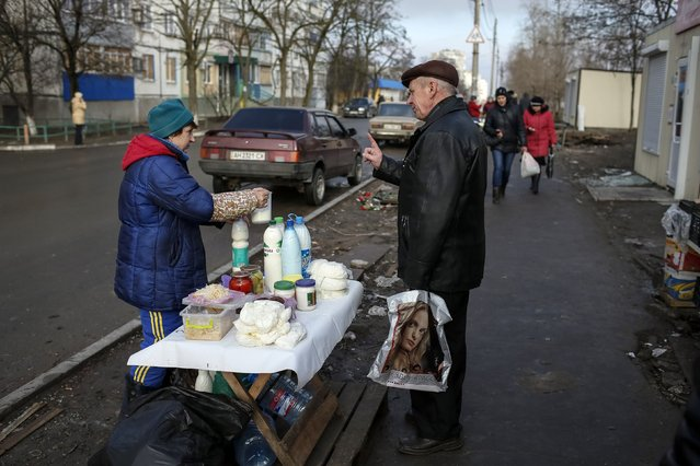 A vendor sells soybean milk on a street at a residential sector affected by shelling in Mariupol, a city on the Sea of Azov, eastern Ukraine February 3, 2015. (Photo by Gleb Garanich/Reuters)