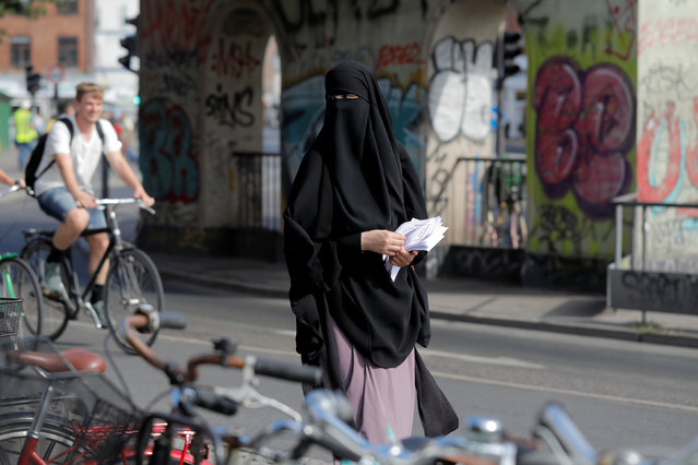 Alaa, 22, member of the group Kvinder I Dialog and wearer of the Islamic clothing the niqab, passes out flyers to promote their group's protest against the Danish face veil ban which will come into effect August 1, 2018, in Copenhagen, Denmark, July 31, 2018. (Photo by Andrew Kelly/Reuters)