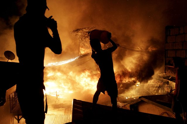 A resident throws water from a bucket on the roof of a house as he tries to extinguish a fire at a residential district, amidst New Year celebrations in Manila January 1, 2016. Local media reports said about 2000 families were rendered homeless after a fire caused by firecrackers gutted houses during New Year celebration in Manila. (Photo by Czar Dancel/Reuters)