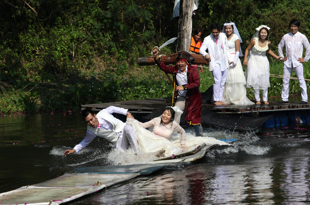 Thai groom and bride, Sorawich Changtor (front L), 28, and Rungnapa Panla (front R), 30, run to escape a man dressed as a pirate as (behind L-R) Prasit Rangsiyawong, 29, Varuttaon Rangsiyawong, 27, Chutima Imsuntear, 37, and Sopon Sapaotong, 41, look on during a wedding ceremony ahead of Valentine's Day in Prachin Buri province, east of Bangkok February 13, 2013. Three Thai couples took part in the wedding ceremony arranged by a Thai resort that aimed to strengthen the relationships of the couples by doing fun activities. (Photo by Kerek Wongsa/Reuters)