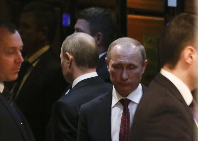 Russia's President Vladimir Putin (2nd R) uses an elevator as he attends a peace summit to resolve the Ukrainian crisis in Minsk, February 12, 2015. (Photo by Vasily Fedosenko/Reuters)