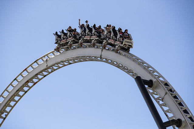 Guests wearing face masks enjoy a ride at the Six Flags Magic Mountain amusement park as it reopens in Valencia, North of Los Angeles, California, USA, 01 April 2021. The park reopened on 01 April at 15 percent capacity which will be increased to 35 percent after one week. (Photo by Etienne Laurent/EPA/EFE)