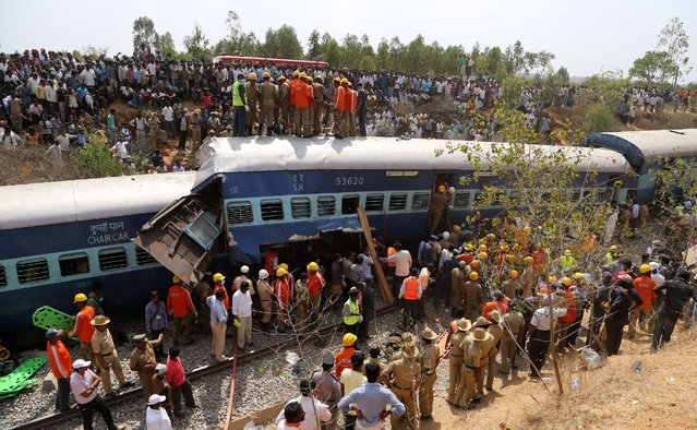 Rescuers and onlookers gather around damaged coaches of a derailed train near Anekal, about 40 kilometers south of Bangalore, India, Friday, February 13, 2015. A train derailed after hitting a boulder that had fallen on the track in southern India on Friday, killing more than 10 people and injuring dozens, officials said. (Photo by Aijaz Rahi/AP Photo)
