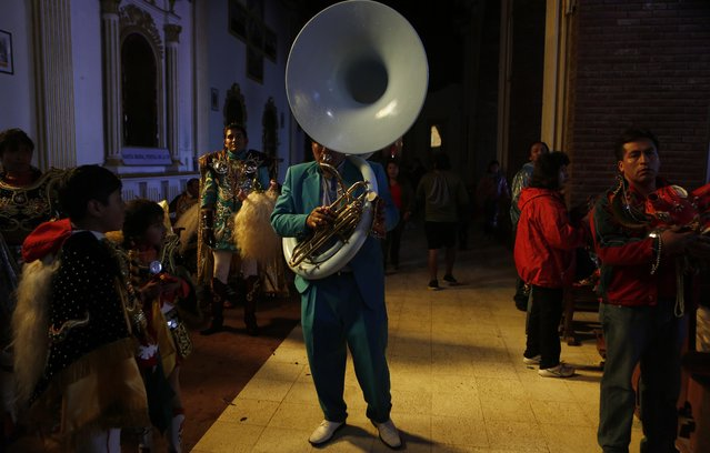 """A musician plays for the patron saint, the """"Virgen del Socavon"""" or """"Virgin of the Mineshaft"""" after parading during Carnival celebrations in Oruro, Bolivia, Saturday, February 14, 2015. (Photo by Juan Karita/AP Photo)"""