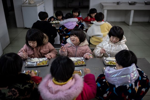 In this picture taken on January 11, 2021, young gymnasts eat dinner in the canteen at the Li Xiaoshuang Gymnastics School in Xiantao, Hubei province. (Photo by Nicolas Asfouri/AFP Photo)