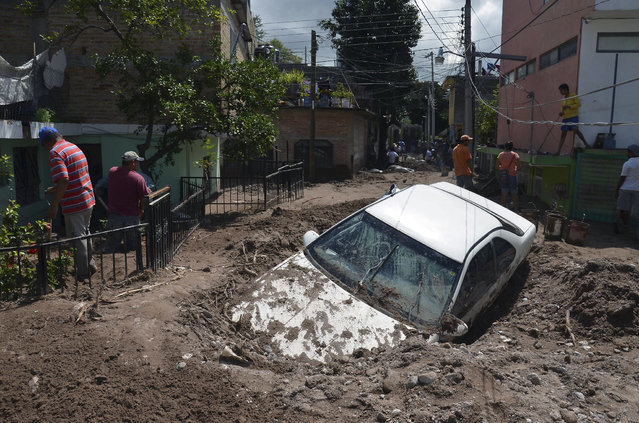 A car lays buried in mud after flooding triggered by Tropical Storm Manuel as residents try to clean up their neighborhood in Chilpancingo, Mexico, Thursday, September 19, 2013. Manuel, the same storm that devastated Acapulco, gained hurricane force and rolled into the northern state of Sinaloa on Thursday before starting to weaken. (Photo by Alejandrino Gonzalez/AP Photo)