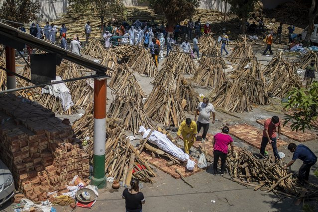 People prepare a funeral pyre for a family member who died of COVID-19 at a ground that has been converted into a crematorium for mass cremation of COVID-19 victims in New Delhi, India, Saturday, April 24, 2021. Indian authorities are scrambling to get medical oxygen to hospitals where COVID-19 patients are suffocating from low supplies. The effort Saturday comes as the country with the world's worst coronavirus surge set a new global daily record of infections for the third straight day. The 346,786 infections over the past day brought India's total past 16 million. (Photo by Altaf Qadri/AP Photo)