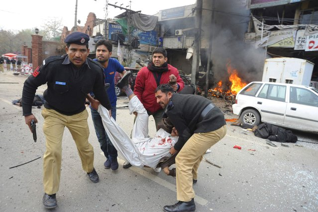 Policemen and residents move a dead body from the site of an explosion outside the police headquarters, in Lahore February 17, 2015. At least seven people died on Tuesday in a large explosion and gunfire at the regional police headquarters in Pakistan's eastern city of Lahore, police said. (Photo by Imran Sheikh/Reuters)