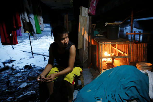 A man passes the time under C-3 bridge in North Bay Boulevard South (NBBS), a Navotas City district of slums and waterways with a high number of drug war deaths, in Manila, Philippines November 3, 2016. (Photo by Damir Sagolj/Reuters)